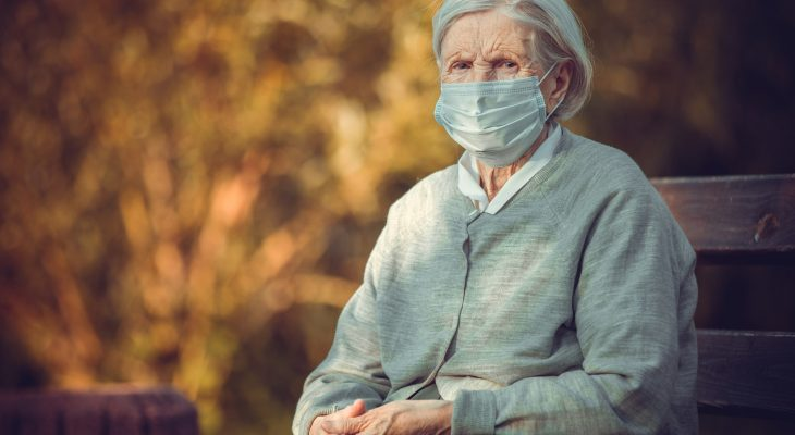 Portrait of senior woman in medical mask sitting on bench
