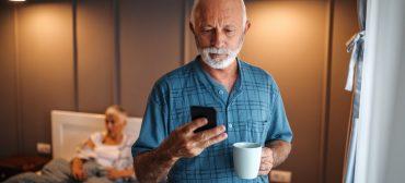 Senior man using smart phone at home