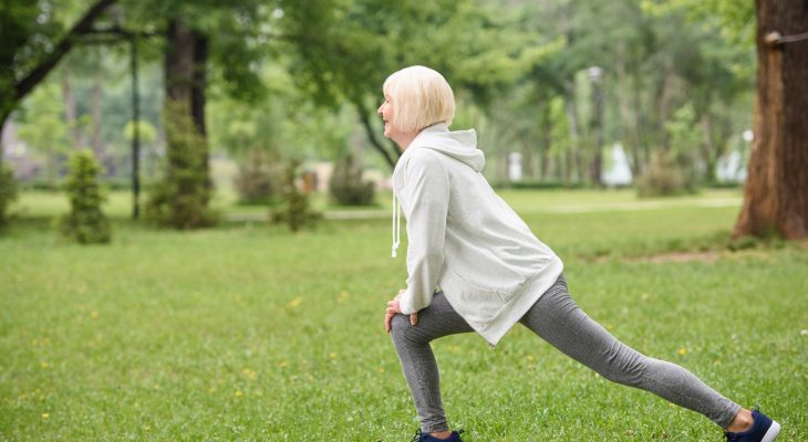 senior sportswoman exercising and doing lunges on lawn in park