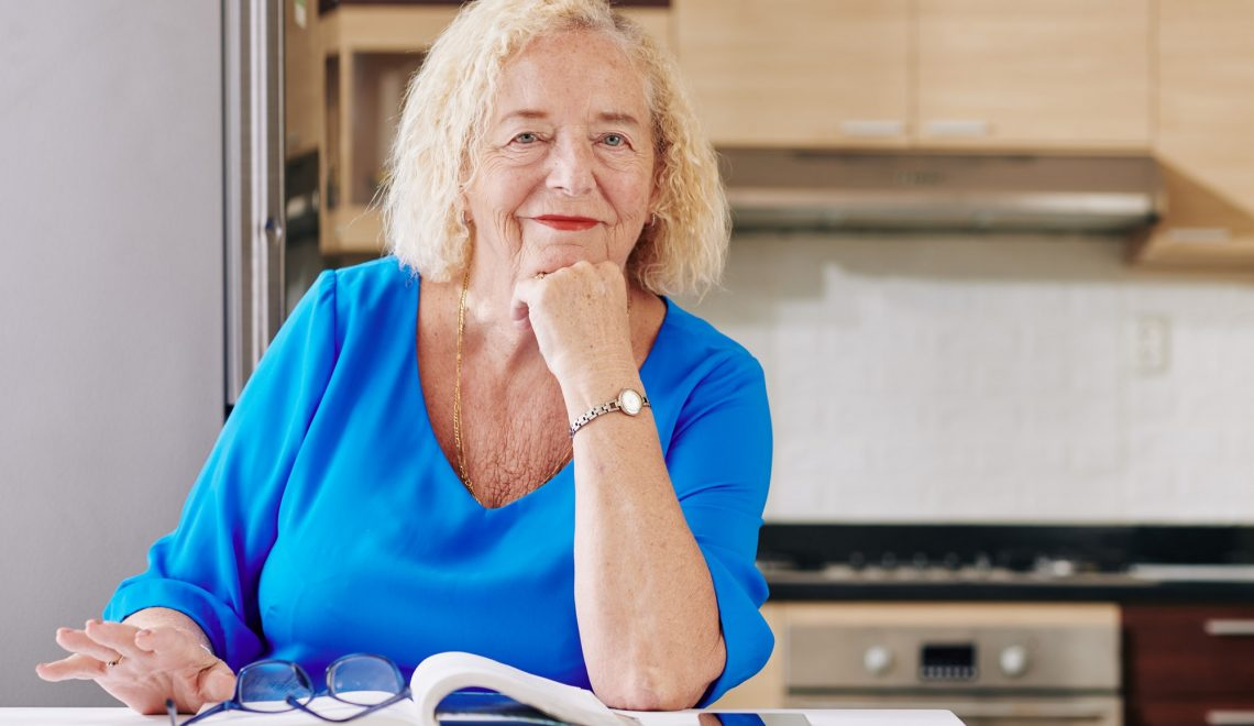 Senior woman reading in kitchen