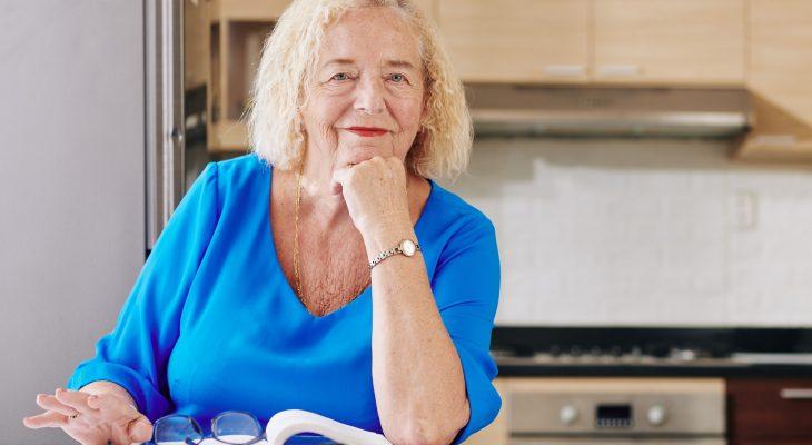 Senior woman reading in kitchen