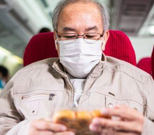 Asian senior man using mobile phone on airplane