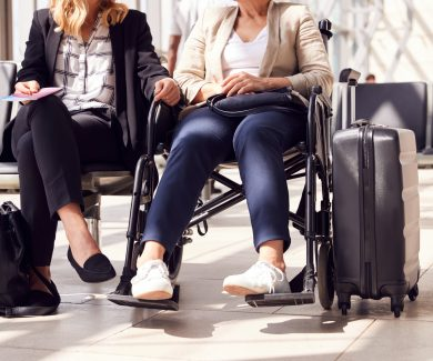 Close Up Of Businesswoman Sitting In Airport Departure With Female Colleague In Wheelchair