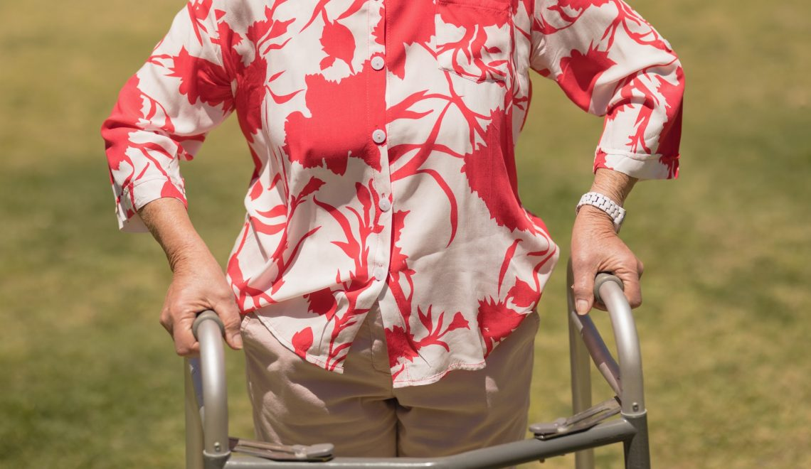 Mid section of disabled senior woman walking with walker in garden on a sunny day