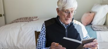 senior man reading a book in his bedroom