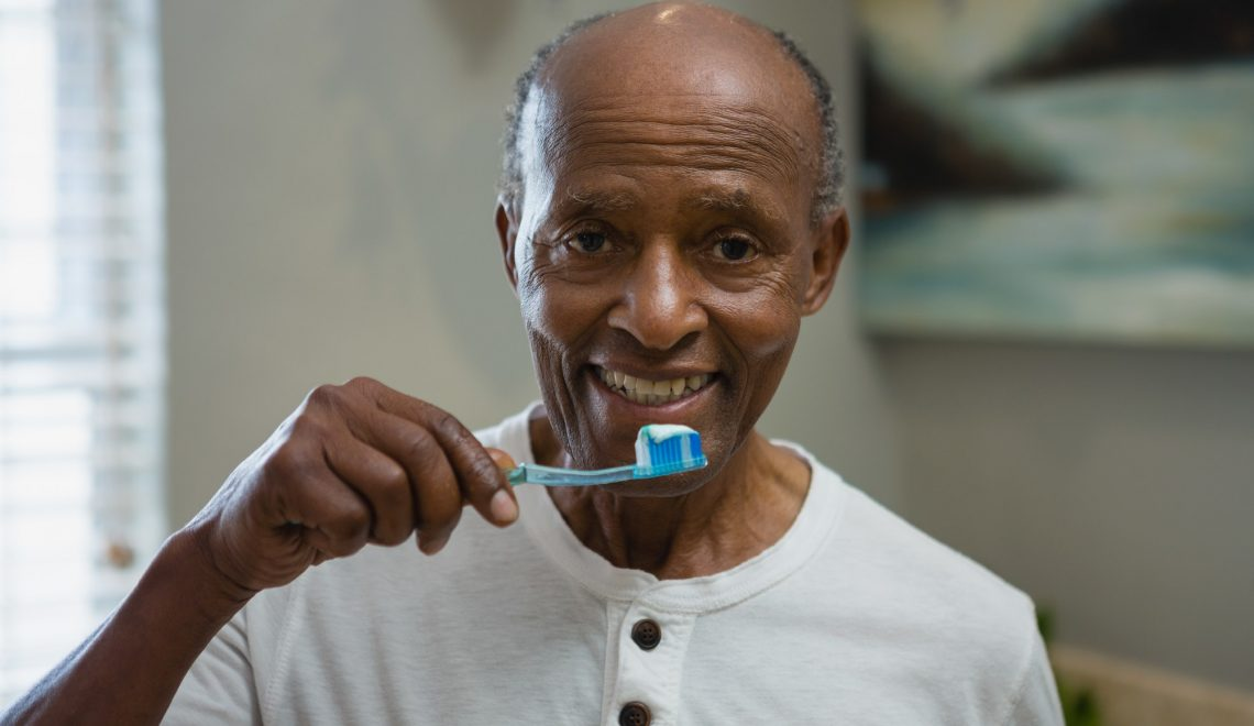 Portrait of senior man brushing teeth in bathroom