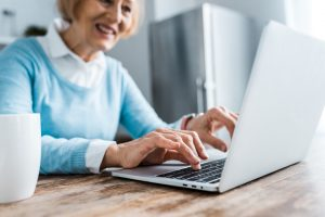 selective focus of smiling senior woman typing on laptop at home