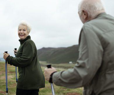 Happy seniors walking with trekking poles