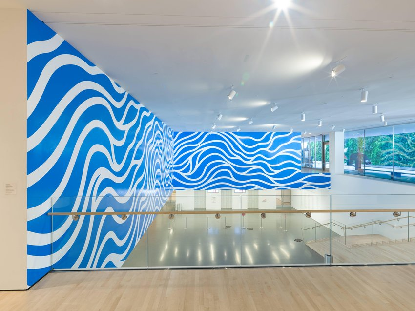 This large piece features wavy white lines on a brilliant blue surface, and resembles rippling waves in azure water. It has been mounted directly onto two adjoining walls, facing the wooden staircase in Schwab Hall. The painting's white lines bend and undulate freely, rolling horizontally along the inside corner. The lines sometimes intersect, but largely run parallel to one another, as if following the same path in a river.