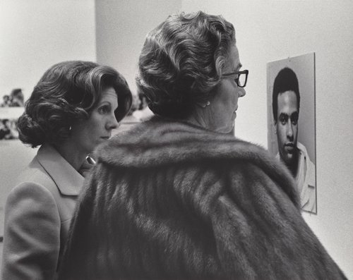 Untitled [Two women looking at Newton portrait, exhibition of A Photographic Essay on the Black Panthers at the De Young Museum, San Francisco, California]