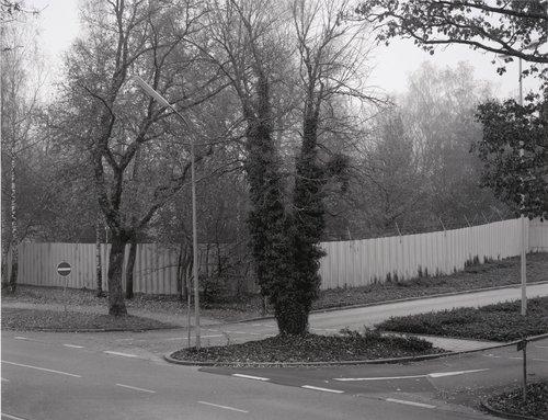 """Linker Teil der Haupteinfahrt, im Hintergrund Parkplatz auf dem so genannten Bunker Hagen (Left Side of the Main Entrance; in the Background is the Parking Area of the So-Called """"Hagen"""" Bunker)"""
