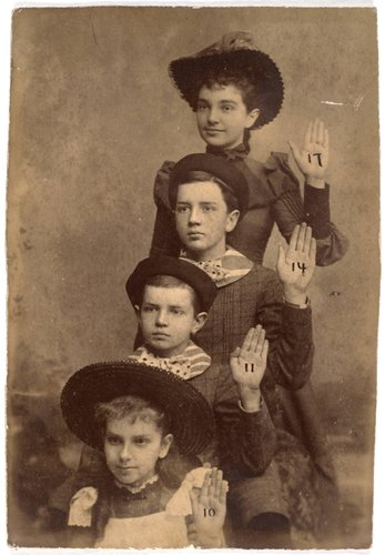 Untitled [Four children with their left hands raised]