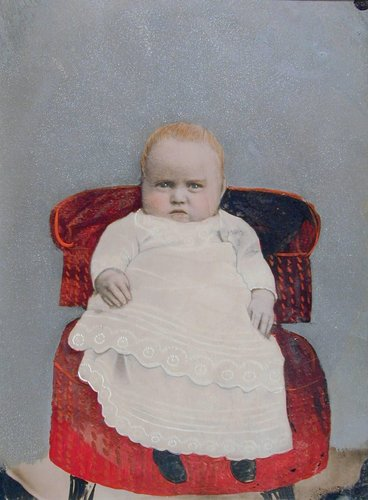 Untitled [Baby on a red velvet chair]