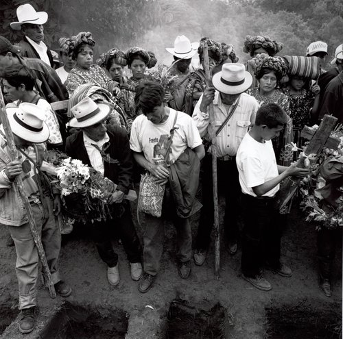 "Sunday, July 29, 2001. With a mixture of grief, joy, and relief, the remains of fifteen are about to be buried in the cemetery of one of the villages. Pablo, who stands at the center and is burying his father who was killed in 1983 by a military patrol, told me this earlier that day: ""The truth is that it's a mixture of sadness and happiness. Sadness to see the remains since they are only bones that you have, in the case of my father. But this moment, today, to still be able to recover part of his body, part of him, even if it's only his remains."" Janlay, Nebaj, Quiché, Guatemala, 2001."