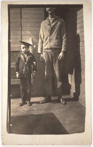 Untitled [Boy in a sailor outfit standing next to a man]