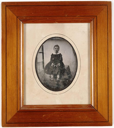 Untitled [Young Girl Wearing a Black Dress, Seated on a Table]