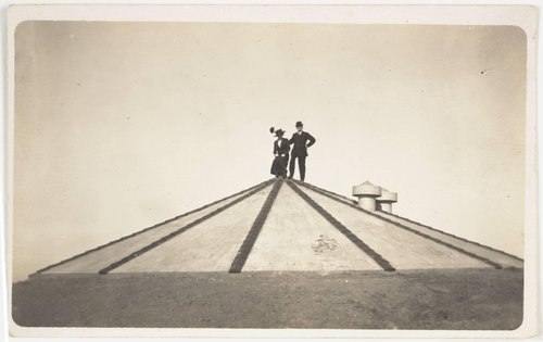 Untitled [Man and woman standing on a pyramid-shaped structure]