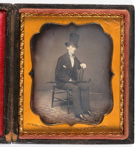 Untitled [Man with top hat and cane sitting in a chair]