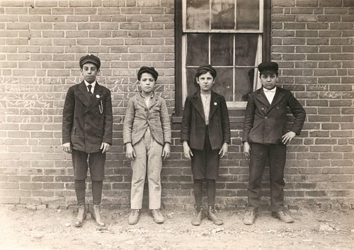 Sweepers and mule-room boys in Royal Mill, River Point, R.I. Boy left hand end, Manuel Mites has been in mill 2 years. Clinton Silvey and Louis Perry (centre boys) have been in mill one year and said they are now 12 years old. Boy on right hand Manuel Sil