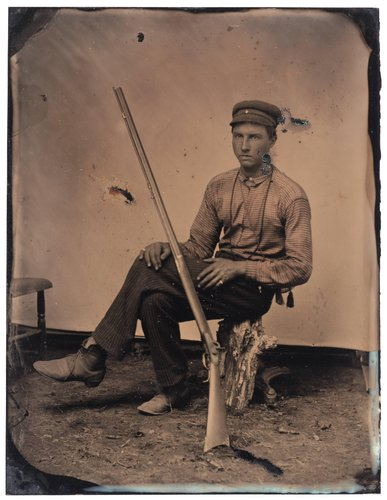 Untitled [Man with a rifle seated on a tree stump]