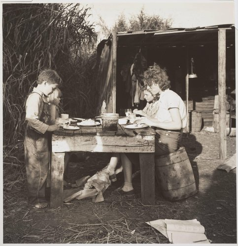 Woman packing house worker from Tennessee with three of her four children eating supper of fried potatoes and corn bread, canned milk. Belle Glade, Florida