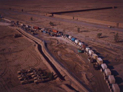 Pakistani 'jingle trucks' end their long journey up from Karachi at the gates of Kandahar Airfield where they wait to be scanned, X-rayed and searched, from the portfolio Burke + Norfolk: Photographs from the War in Afghanistan by John Burke and Simon...