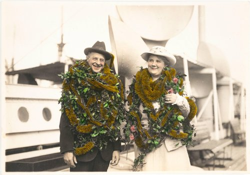 Untitled [Man and woman wearing leis and posing on a ship]