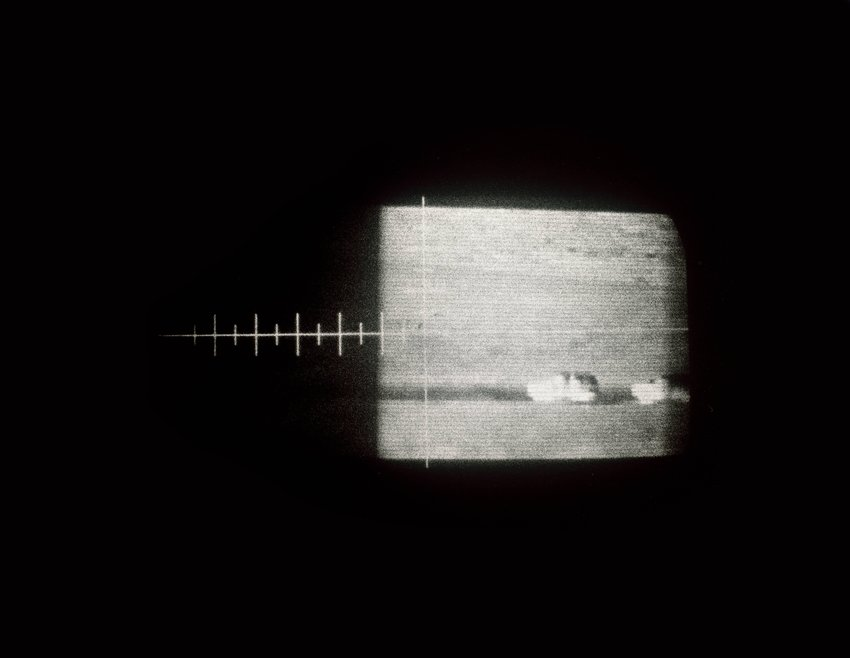 image of 'Ghostly view thru an older U.S. military version, truck-mounted, cryogenic-cooled, thermal infrared imaging scope showing U.S. Border Patrol vehicles moving on a dirt road along the U.S./Mexico Border'