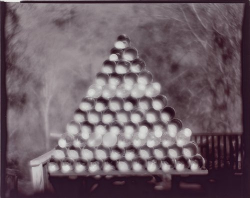 Untitled (tin cans stacked in a pyramid shape)