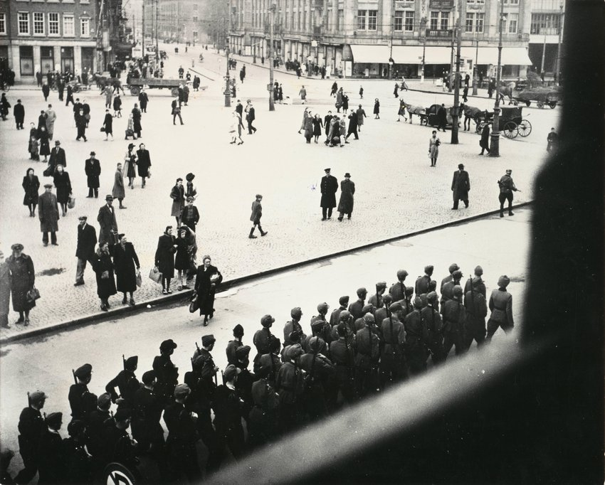 image of 'Laatste groep Duitse soldaten marcheert over de Dam, kort voor de intocht van de Canadezen (The last German troops march across Dam Square shortly before the arrival of the Canadians)'