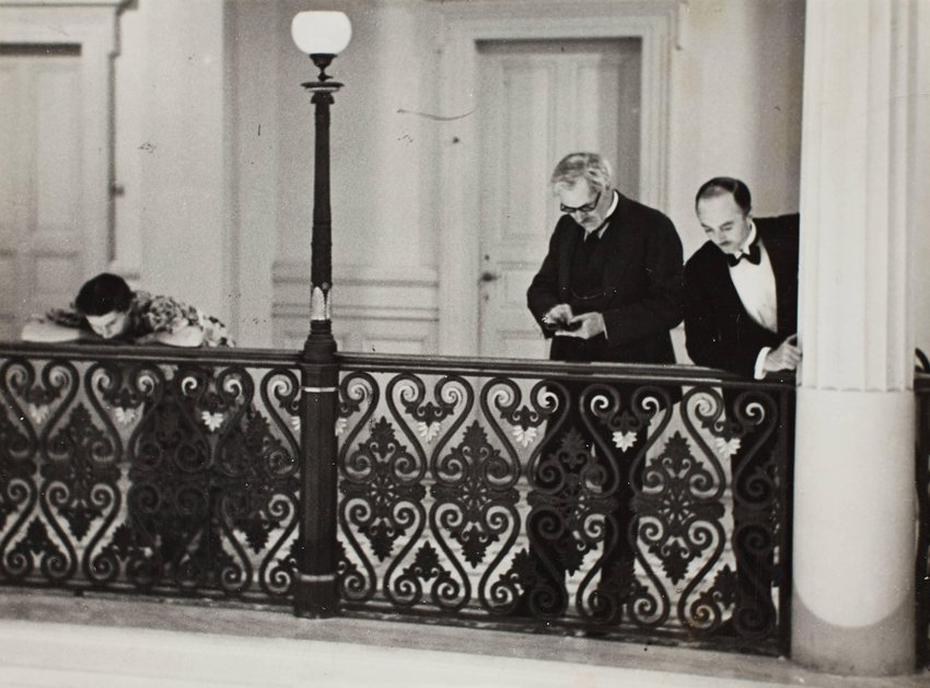 image of 'British statesman Ramsay MacDonald with his daughter Isabel and his secretary Mr. Butler, looking down from hotel balcony as he watches French Premier Édouard Herriot in the lobby during the Lausanne Reparation Conference, Switzerland.'