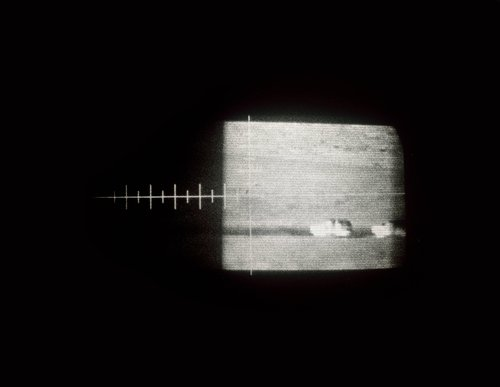 Ghostly view thru an older U.S. military version, truck-mounted, cryogenic-cooled, thermal infrared imaging scope showing U.S. Border Patrol vehicles moving on a dirt road along the U.S./Mexico Border