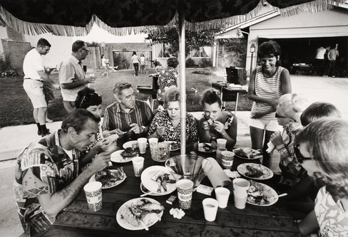 "Image for artwork ""This is our second annual Fourth of July block party. This year thirty-three families came for beer, barbequed chicken, corn on the cob, potato salad, green salad, macaroni salad and watermelon. After eating and drinking [...]"" From the series Suburbia"