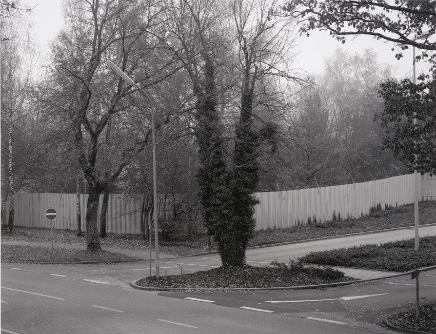"""image of 'Linker Teil der Haupteinfahrt, im Hintergrund Parkplatz auf dem so genannten Bunker Hagen (Left Side of the Main Entrance; in the Background is the Parking Area of the So-Called """"Hagen"""" Bunker)'"""