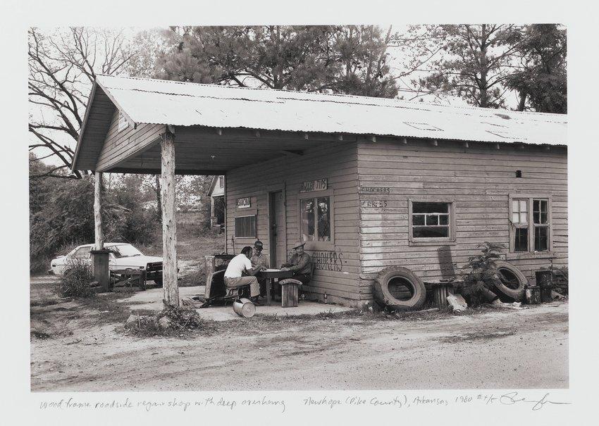 image of 'Wood frame roadside repair shop with deep overhang, Highway 70, Newhope (Pike County), Arkansas'