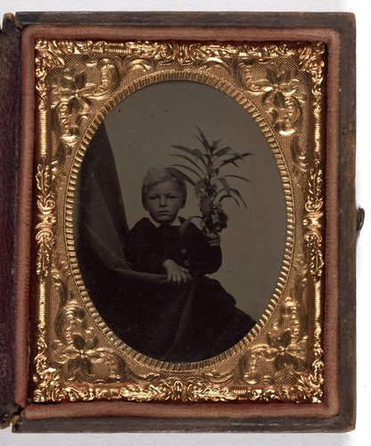 Untitled [Portrait of a blonde boy holding a plant]
