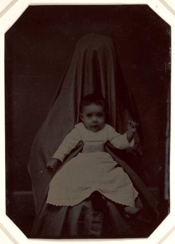 Untitled [Baby held by a person draped with black cloth so as to go unnoticed]