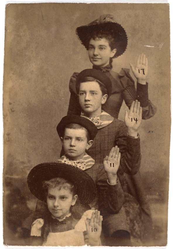 image of 'Untitled [Four children with their left hands raised]'
