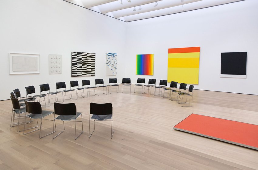 A semi-circle of empty chairs is set up in a white gallery filled with colorful paintings