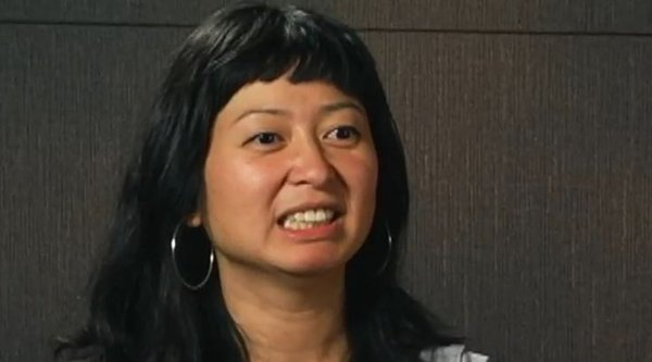 An Asian woman speaking before a grey background