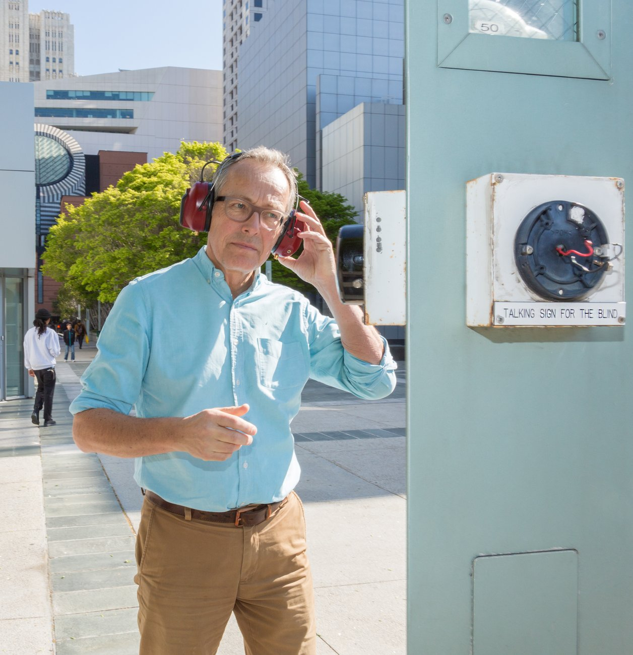 A Caucasian man wearing red headphones and glasses walks toward an electrical meter on the street, Kubisch Soundtracks