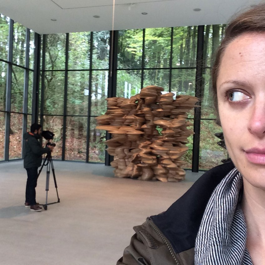 A selfie of a woman with a cameraman in the background in the indoor exhibition space at Tony Cragg's Skulpturenpark Wuppertal
