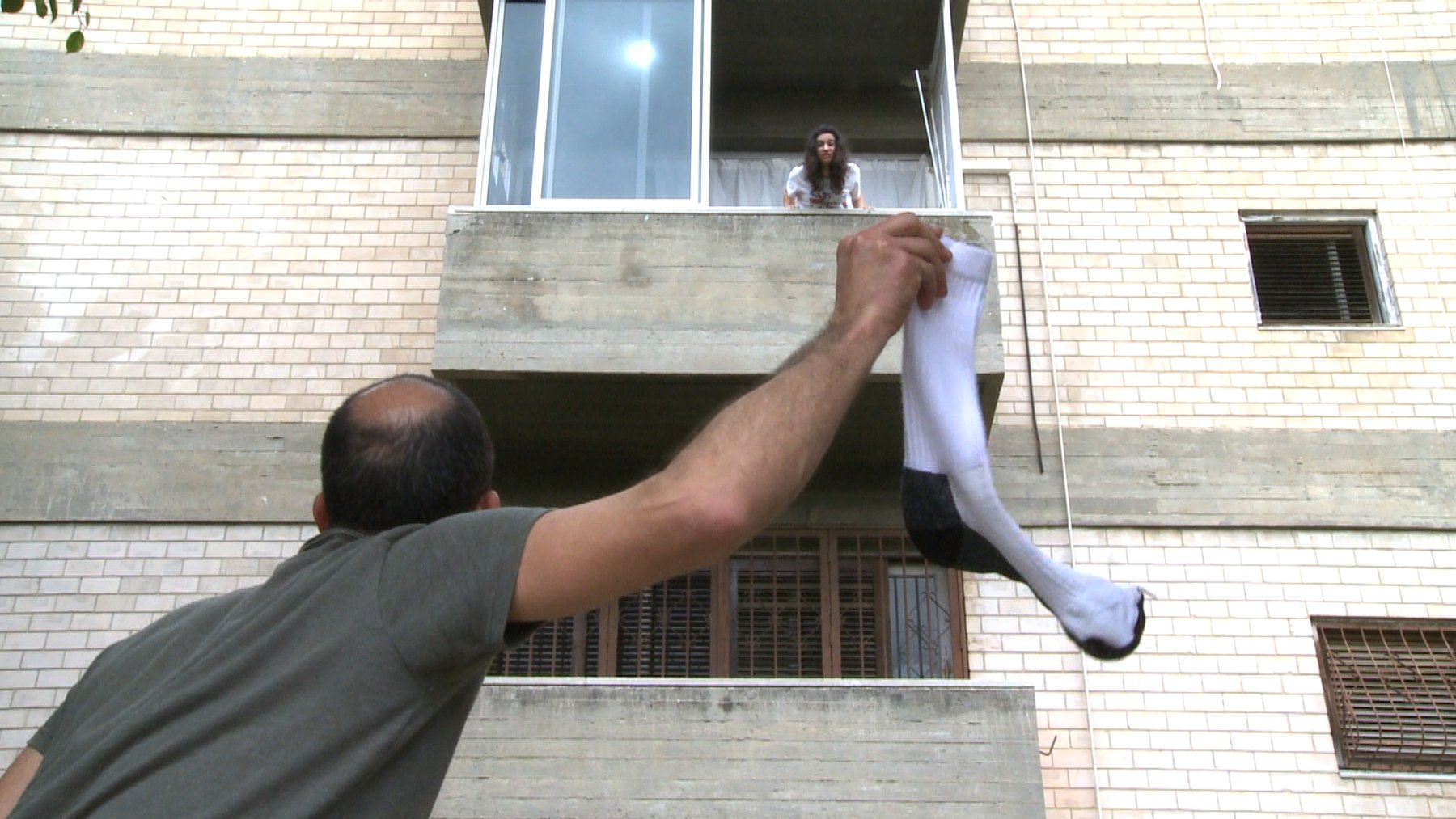A balding man holds a white tube sock up as a woman looks down from a window above, Ben Ner Soundtracks