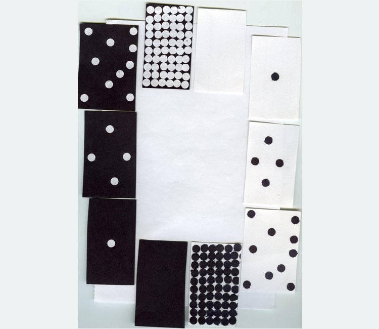 An assortment of handmade black and white paper dominoes with irregular dots