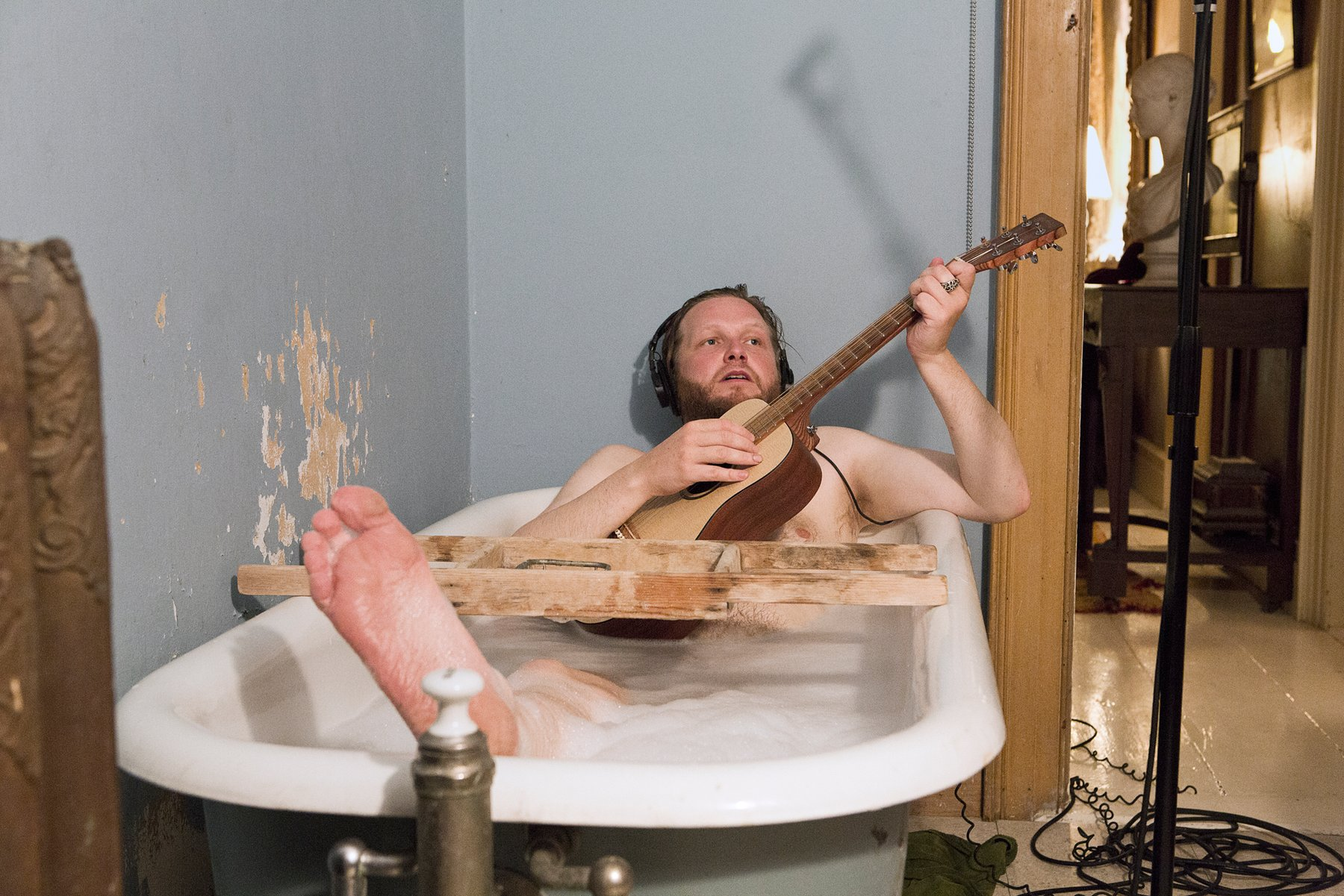 A naked Caucasian man plays the guitar in a bathtub, Kjartansson