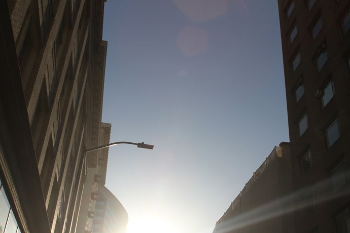steet lamp sky and sun between two buildings from below