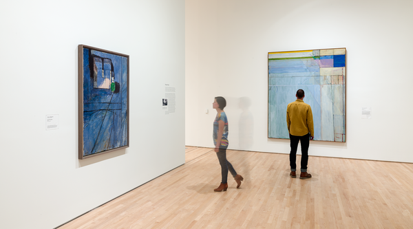 A woman walks toward a blue painting while a man stands in front of a large tranquil painting