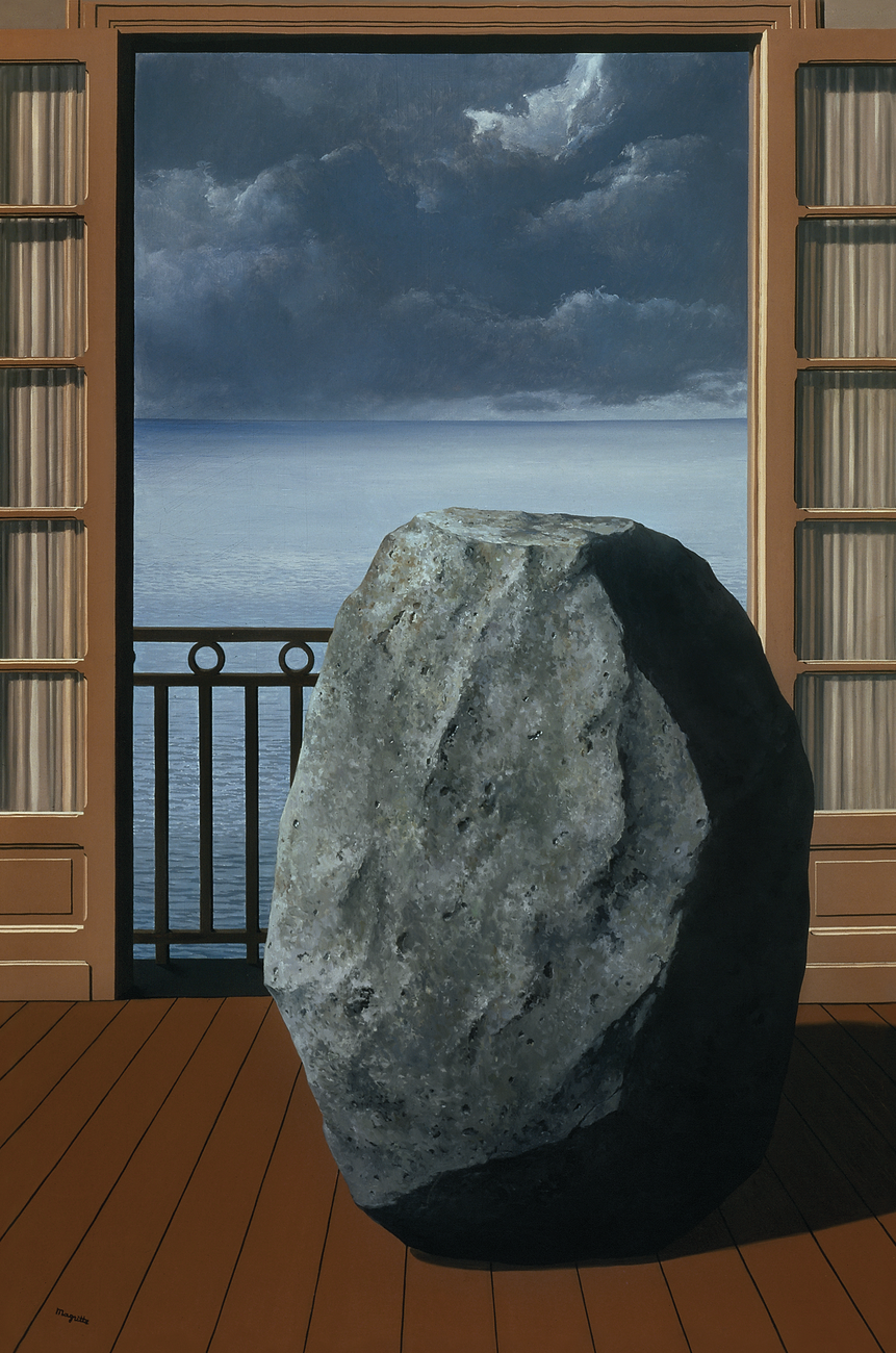 A large gray boulder on a wooden floor next to an open door overlooking a veranda with an ocean view
