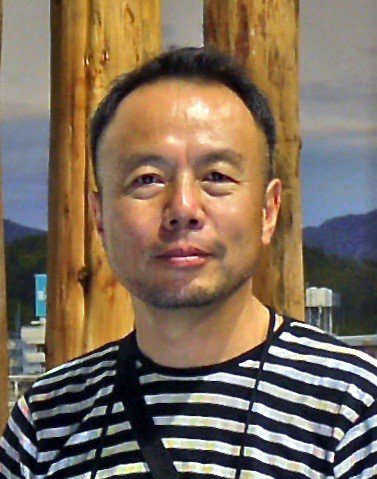 Color photograph portraying an Asian man wearing a striped shirt, Hatakeyama