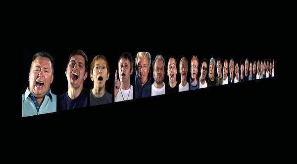 A series of faces with their mouths open are projected onto a black wall receding into the distance